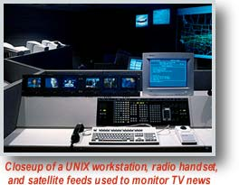 Closeup of a UNIX workstation, radio handset and satellite feeds used to monitor TV news