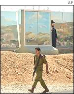 Israeli soldier and Orthodox Jew in front of cement block barriers in Gilo