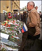 A Russian kneels amid floral tributes outside the US embassy in Moscow