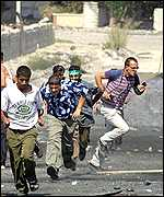Palestinians run for cover during clashes with Israeli troops