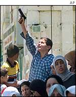 A Palestinian boy holds a toy gun