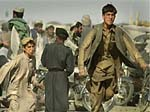 Two young Afghan refugees sprint past a Pakistani border guard.
