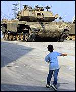 A boy throws stones at an Israeli tank in Hebron