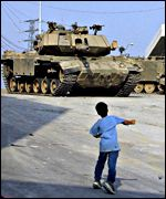 Palestinian child throws stones at an Israeli tank