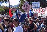 SF Rally photo, big puppet of George Bush, his sign says, Terrorism? Who Me? Kill Civilians?