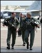 President George W. Bush walks across the tarmac with NFO Lt. Ryan Phillips to Navy One, an S-3B Viking jet, at Naval Air Station North Island in San Diego Thursday, May 1, 2003. Flying to the USS Abraham Lincoln, the President will address the nation and spend the night aboard ship. White House photo by Susan Sterner