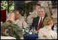 President George W. Bush sits down for lunch with military personnel at MacDill Air Force Base in Tampa, Florida, Wednesday, March 26, 2003. White House photo by Paul Morse.