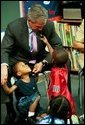 During a tour of Highland Park Elementary School in Landover, Md., President George W. Bush plays with children at the school's Head Start Center where he discussed strengthening America's Head Start Program Monday, July 7, 2003. White House photo by Paul Morse.