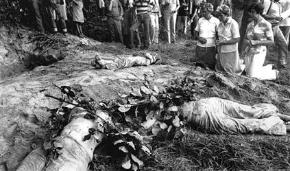 Nuns pray over the bodies of four American sisters killed by the military in El Salvador in 1980
