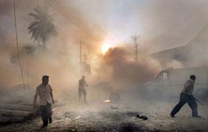 People get away from the smoke and flames of a car bombing in Baghdad, Iraq. Allison Long, Kansas City Star