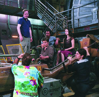 "Joss Whedon (standing)  directs Nathan Fillion, Adam Baldwin and Summer Glau on the set of Universal's ""Serenity."""