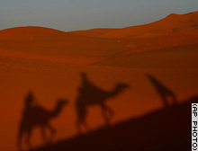 The shadows of tourists are seen as they ride camels in Merzouga, Morocco along what is called the route of a thousand kasbahs in the Atlas Mountains.