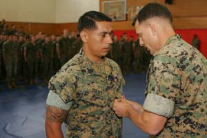 CAMP HANSEN, OKINAWA, Japan – Staff Sgt. Logan Cortes, the Interim Fast Attack Vehicle section leader for Company G, Battalion Landing Team 2nd Battalion, 1st Marine Regiment, receives the Bronze Star with combat distinguishing device from Lt. Col. Francis Donovan, BLT 2/1 commanding officer, during an award ceremony here, May 15. On Nov. 15, 2005, during Operation Iraqi Freedom, Cortes rushed into an insurgent-held house to rescue a wounded Marine who could not get out on his own. BLT 2/1 is the ground combat element of the 31st Marine Expeditionary Unit.
