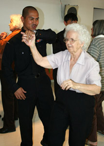BRISBANE, Australia – Navy Petty Officer 2nd Class Rolando Samortin dances with a resident of Wesley Mission elderly home June 7. USS Tortuga (LSD 46) crew members and Marines of the 31st Marine Expeditionary Unit, 3rd Marine Expeditionary Brigade visited the home during a four-day port visit here. Tortuga, along with USS Essex (LHD 2) and USS Juneau (LPD 10) both embarked with Marines of the 3rd MEB, was in Brisbane prior to what will be the start of the at-sea component of Talisman Saber 2007, a joint and combined training exercise between the United States and Australia that will involve more than 32,000 military members from both nations, improve interoperability and enhance the military alliance between the two countries. Photo by: Seaman Brandon A. Myrick, USS Tortuga