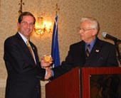 Deputy Secretary Alex Azar accepts a commemorative medallion honoring the 117th Anniversary of the Public Health Service Commissioned Corps from Rear Admiral Jerrold M. Michael (Ret.), President of the PHS Commissioned Officers Foundation.
