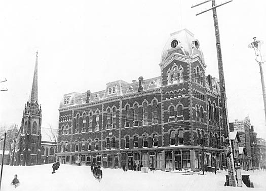 Children slide in the snow outside the Old Town Hall on Atlantic Square. Congregational Church in the background.