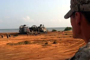 Corporal Dan E. Larson, a landing support specialist from Combat Logistics Battalion-26, looks on as Marines and Sailors from the 26th Marine Expeditionary Unit offload from a Landing Craft Air-Cushioned at a beach near Camp Lemonier, Djibouti, Feb. 5, 2007.  The LCACs, from Assault Craft Unit-4, carried the MEU's troops ashore from the ships of the Bataan Strike Group to participate in Exercise Image Nautilus.    Photo by: Cpl. Jeremy Ross.