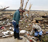 Southern States Devastated by Killer Storms // Clay & Seavia Dixon pick through what is left of their tornado-damaged home in Atkins, Ark. (© Mike Wintroath/AP)