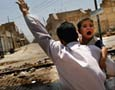 Iraqi Man Carrying Child, Waving to Snipers