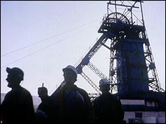 Silhouette of miners against pithead