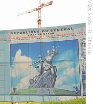 A billboard below the construction site shows a depiction of the Monument to the African Renaissance