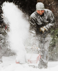 A man operates a snowblower on the sidewalk during a snowstorm in Toronto.