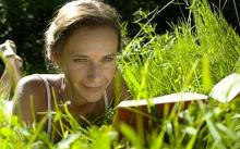 Woman reading book in long grass - Best deals of the day: Books