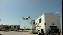 A plane lands on the runway at Los Angeles International Airport, behind mobile homes for airline workers