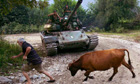 A man pulls a cow in front of an Abkhaz tank