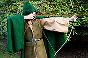 Man with bow and arrow dressed in brown jacket with green cape and hood.