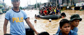 Residents are evacuated by police on rubber boats during flooding in Cainta Rizal, east of Manila