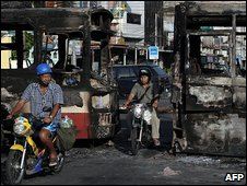 Motorists drive through the burnt remains of buses on a Bangkok street