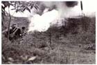 An Australian soldier of the 7th Division finishes off an 'enemy' foxhole during flame warfare exercises, Danbulla, Atherton Tableland, April 1945.  Beginning with the 9th Division in 1943 the Atherton Tablelands provided Australian units with the opportunity for large-scale and realistic tropical warfare training prior to deployment to the battlefields of New Guinea and Borneo.  Throughout 1944 and 1945 already experienced units returning from New Guinea were sent to Atherton to refit and acquire the latest techniques and equipment before returning to combat.