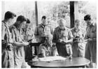 Major General Gordon Bennett (sitting) briefing war correspondents on the first clash between Australians and Japanese, Malaya, January 1942.  After the fall of Singapore and his return to Australia Bennett wrote a series of reports on the campaign that were circulated amongst Australian officers in Australia and New Guinea.  However their usefulness was limited as the terrain of Malaya bore little resemblance to the conditions encountered in New Guinea.
