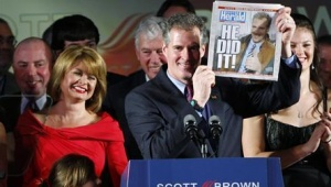 Republican Senator-elect Scott Brown holds up a copy of the Boston Herald announcing his victory as he celebrates with his wife Gail Huff (L) after defeating Democrat Martha Coakley in the Senate race to replace the the late Senator Ted Kennedy at Brown's victory rally in Boston January 19, 2010. Brown won a bitter U.S. Senate race in Massachusetts on Tuesday, dealing a sharp blow to President Barack Obama's legislative agenda and casting doubt on the fate of his sweeping healthcare overhaul. Credit: REUTERS/Brian Snyder