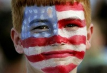 A boy with his face painted in stars and stripes awaits the arrival of then President George W. Bush at a campaign rally in Florida, October 31, 2004.  REUTERS/Kevin Lamarque