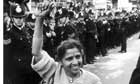 A woman holds fist of victory as she passes line of policemen