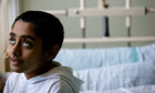 A boy sits on his hospital bed