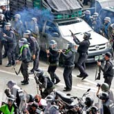 """Riot police fire into the air to try and disperse anti-government """"red-shirt"""" protesters on a highway near the old airport in Bangkok"""
