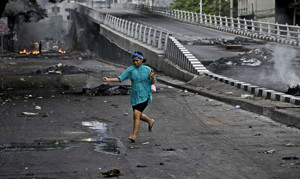 A resident runs in a street near Ding Daeng intersection in Bangkok on May 17, 2010. Thousands of protesters in the Thai capital defied a deadline to leave their fortified encampment despite the threat of a crackdown after street clashes that left at least 35 people dead.