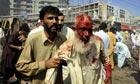 9 October 2009: People help an injured person out of the bombing site in Peshawar