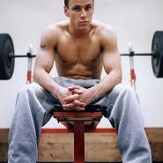 Fit young man sitting in front of a dumbbell