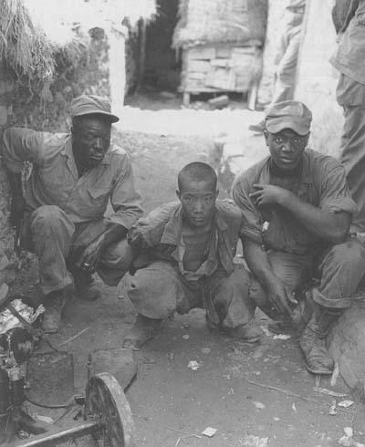 Two American soldiers with a North Korean prisoner of war, 5 August 1950