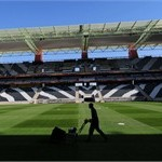 A worker cuts the grass of the field of the Mbombela Stadium, in Nelspruit