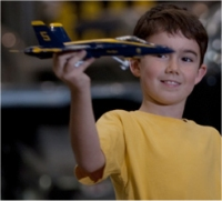 child with model Navy plane