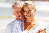 Double head shot of mature couple on beach in white