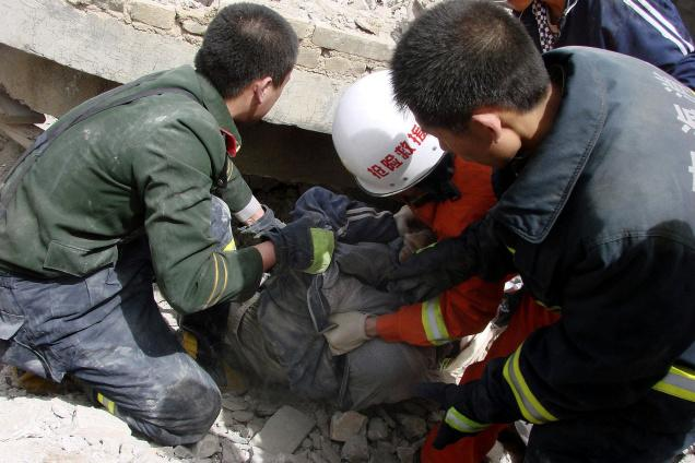 Rescue workers pull out a person from a building, which collapsed during the earth quake, in Yushu county in western China's Qinghai province on Wednesday.
