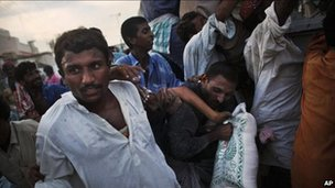 Pakistanis grab a bag of food aid on the road outside of Sukkur, in Sindh province, Pakistan on 17 August, 2010