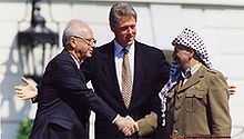 A stolid balding man in a dark suit on the left shakes the hand of a smiling man in traditional Arab headdress on the right. A taller, younger man stands with open arms in the center behind them.