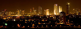 Night time picture of Tel Aviv showing many skyscrapers illuminating the city skyline